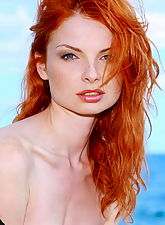 Fiery redhead girl strips naked at the beach
